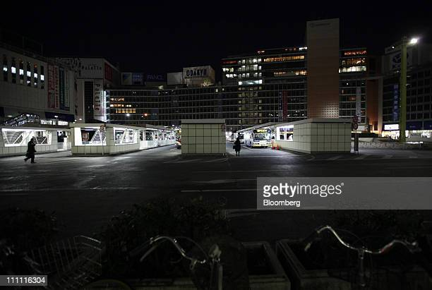 People walk past a bus terminal at night in the Shinjuku district of Tokyo Japan on Monday March 28 2011 As Tokyo Electric Power Co the utility...