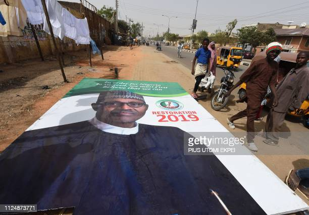 People walk past a campaign billboard for the candidate of the ruling All Progressives Congress President Mohammadu Buhari lying on the road in Kano...