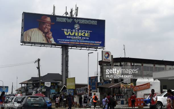 People walk past a campaign billboard of gubernatorial candidate of the Peoples Democratic Party in Rivers State and incumbent Rivers State's...