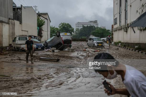 People walk past a car that was overturned by flooding after the nearby Kuma River burst its banks, on July 5, 2020 in Hitoyoshi, Japan. Around 16...