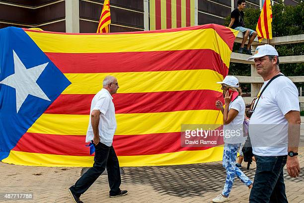 People walk past a Catalan ProIndependence flag before a ProIndependence demonstration celebrating the Catalan National Day on September 11 2015 in...