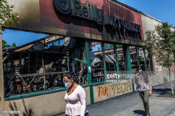 People walk past a charred wreckage of an Auto parts store destroyed during last week's rioting which was sparked by the death of George Floyd on...