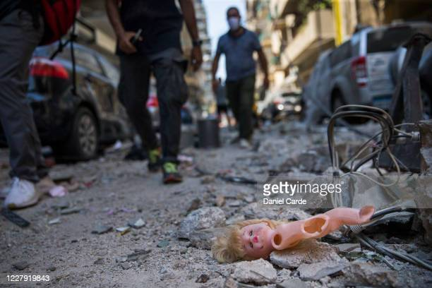 People walk past a childs doll that was blown out of a nearby building after a massive explosion which occurred a day before on Aug 5 2020 in Beirut...