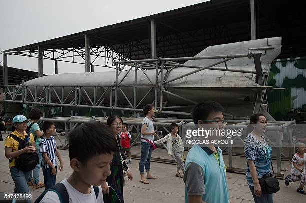 People walk past a Chinese DF1 surfacetosurface missile on display at the military museum in Beijing on July 15 2016 The commanders of the US and...