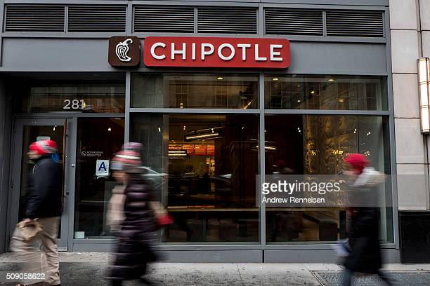 People walk past a Chipotle restaurant on Broadway in Lower Manhattan on February 8 2016 in New York City The Mexican food chain is closing stores...