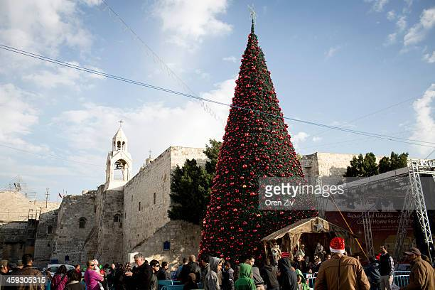 People walk past a Christmas tree outside the Church of the Nativity traditionally believed to be the birthplace of Jesus Christ on December 25 2013...