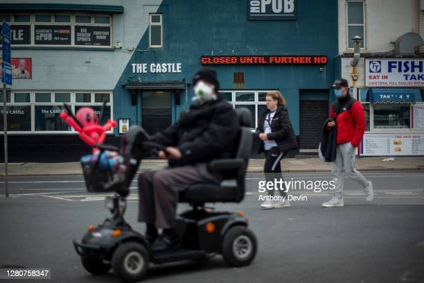 People walk past a closed down pub in the town center on October 17, 2020 in Blackpool, England. Lancashire has entered tier 3 of the government's...