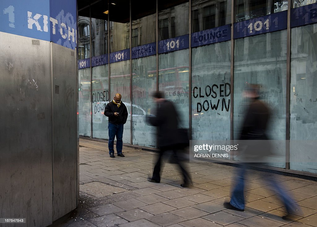 People walk past a closed down restaurant in London on December 4, 2012.