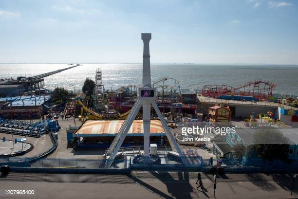 People walk past a closed leisure park Adventure Island due to the Coronavirus pandemic on Mother's day March 22 2020 in Southend on Sea England With...