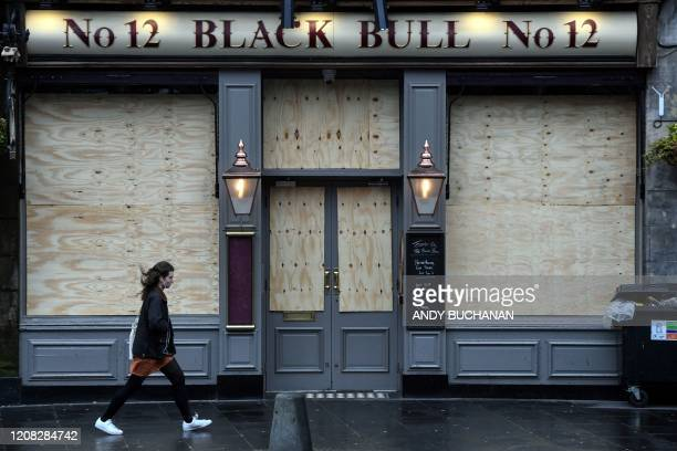 People walk past a closed pub in The Grassmarket Edinburgh Scotland on March 26 2020 after the government ordered a lockdown to help stop the spread...