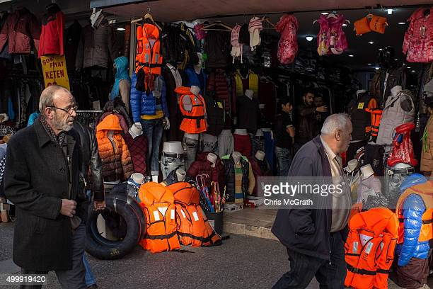 People walk past a clothing store selling lifejackets to migrants and refugees arriving in Izmir on December 4 2015 in Izmir Turkey The flow of boats...