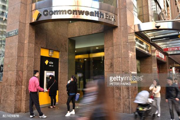 People walk past a Commonwealth Bank branch in the central business district of Sydney on August 8 2017 Australia's Commonwealth Bank said on August...