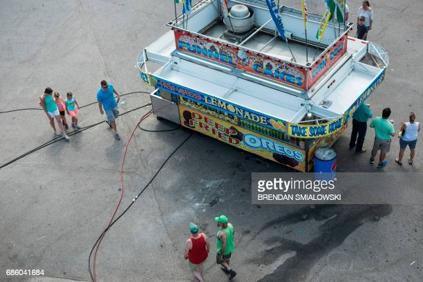 People walk past a concession stand during the Got to Be NC Festival on the North Carolina State Fairgrounds on May 20 2017 in Raleigh North Carolina...