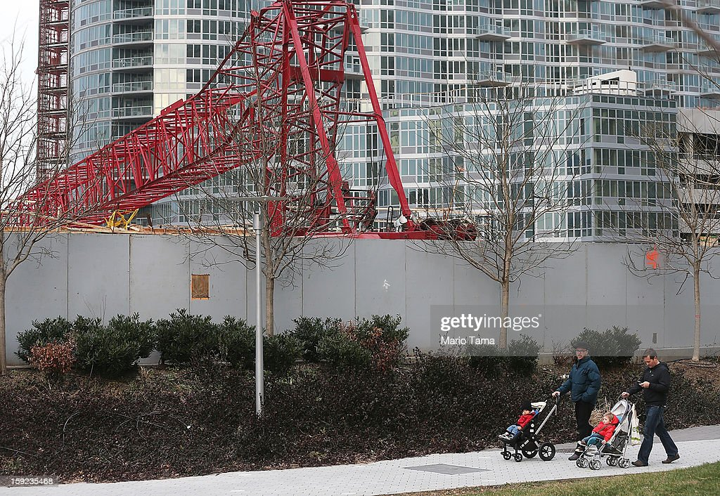 People walk past a construction crane after it collapsed on January 9, 2013 in the Queens borough of New York City. The crane collapse injured seven construction workers on the site in the Long Island City neighborhood.