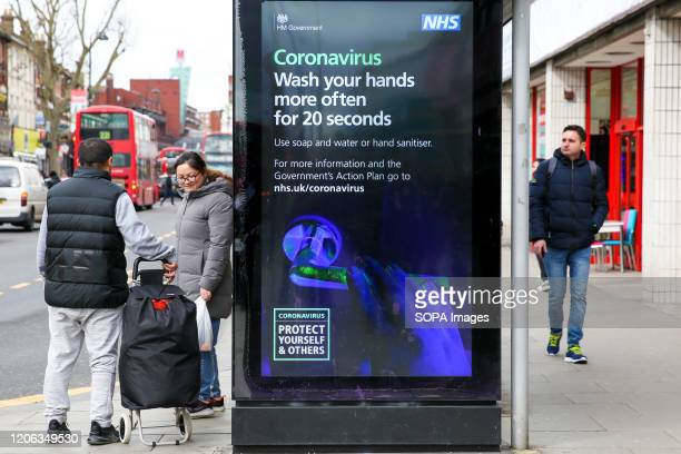 People walk past a Coronavirus public information campaign poster in London, which focuses on hand washing. Five coronavirus victims have died and...