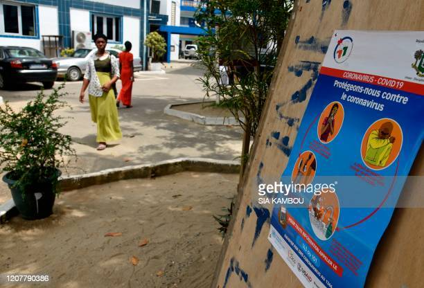 People walk past a COVID-19 coronavirus awareness poster in the courtyard of a church that is closed for worship in Abidjan on March 20, 2020.