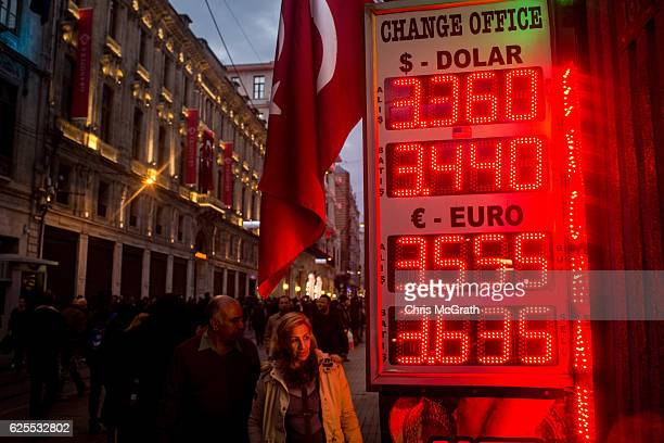 People walk past a currency exchange board showing the US Dollar and Euro rates against the Turkish Lira on November 24, 2016 in Istanbul, Turkey....