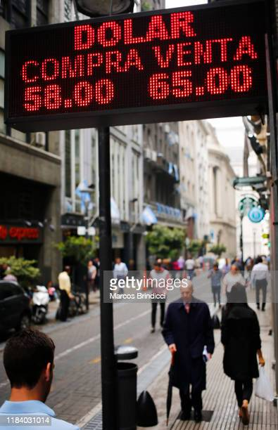 People walk past a currency exchange house showing updated prices of Dollars Brazilian reais Chilean pesos and Euros on October 28 2019 in Buenos...