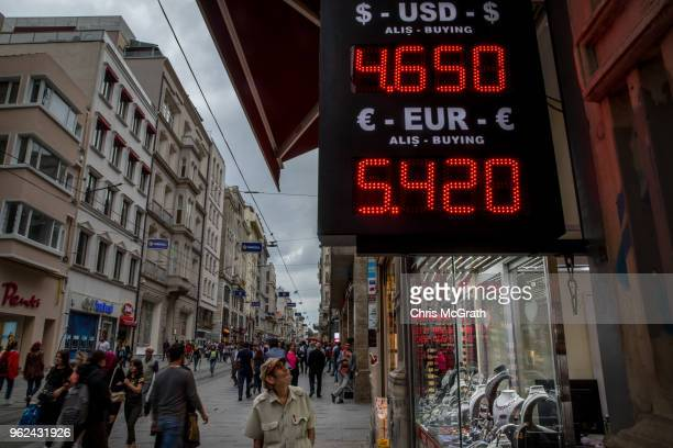 People walk past a currency exchange office showing the rates for USD and Euros against the Turkish Lira on Istanbul's famous Istiklal shopping...