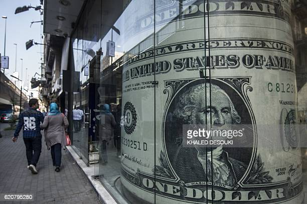 People walk past a currency exchange shop displaying a giant US dollars banknote in downtown Cairo on November 3 2016 Egypt floated the country's...