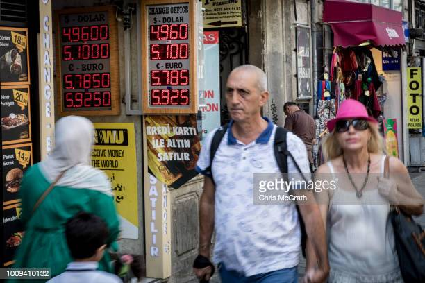 People walk past a currency exchange sign on August 2 2018 in Istanbul Turkey The Turkish Lira dropped to a record low passing 5 TL to the dollar...