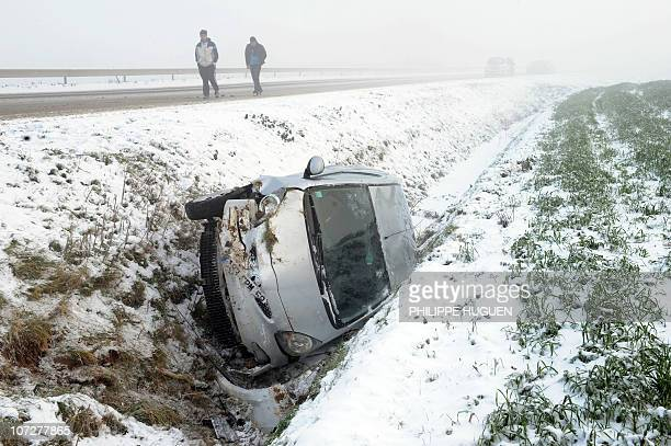 People walk past a damaged car in a ditch in the snowed up northern France countryside on December 3 2010 in ErquinghemLys AFP PHOTO PHILIPPE HUGUEN