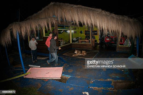 People walk past a damaged restaurant in Concon some 110 kilometers northwest of Santiago after a massive earthquake on September 16 2015 The...