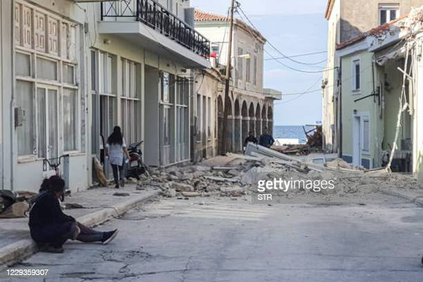 People walk past a destroyed house after an earthquake in the island of Samos on October 30, 2020. - A powerful earthquake hit Greece and Turkey on...