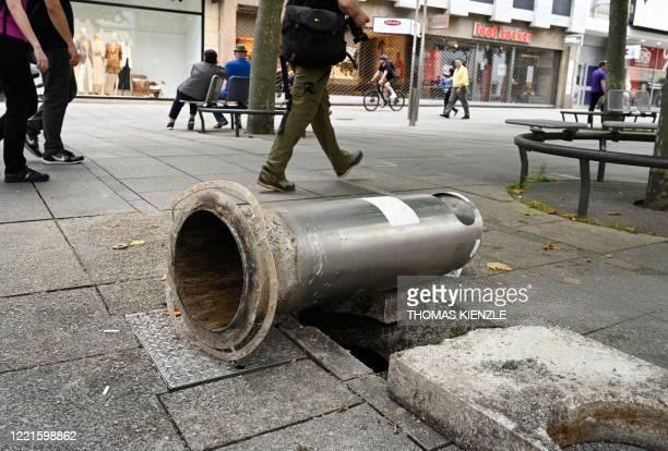People walk past a destroyed waste bin in a pedestrian aerea in Stuttgart, southern Germany on June 21, 2020. - Hundreds of people ran riot in...