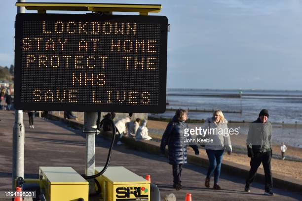 """People walk past a digital public safety notice saying """"Lockdown, Stay At Home, Protect The NHS, Save Lives"""" along the seafront at Westcliff on..."""