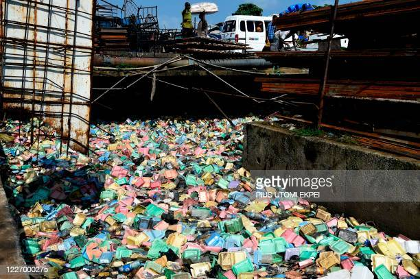 People walk past a drainage channel blocked with disposable foam food take away containers in Lagos, on July 13, 2020. - State officials responsible...
