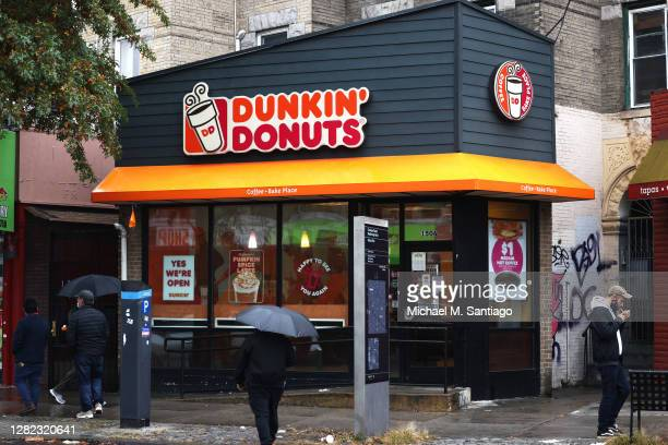 People walk past a Dunkin' store on October 26, 2020 in New York City. The Dunkin' Brands, the parent company of the Dunkin' and Baskin Robbins...