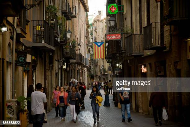 People walk past a estelada or pro independence flag hanging from a balcony in Barcelona downtown Spain on 25 October 2017 Spanish government aims to...