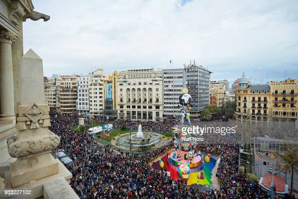 People walk past a Falla at Plaza del Ayuntamiento after the 'Mascleta' an explosive barrage of firecrackers and fireworks during Las Fallas Festival...