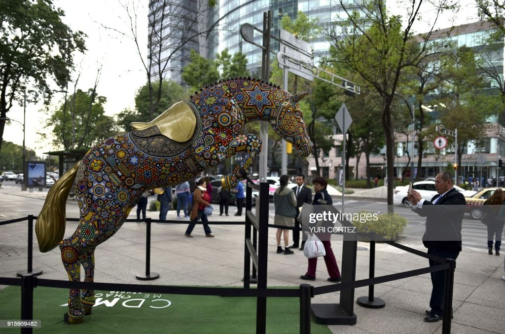 People walk past a fiberglass horse sculpture worked in Huichol art and placed along Reforma avenue as part of an exposition called 'the world's biggest Huichol exhibit', in Mexico City, on February 8, 2018. One hundred Wixarikas indigenous artists from the social and cultural company Paricuta made 10 monumental works of art inspired by sports and nature, which were put on public display on the street. /