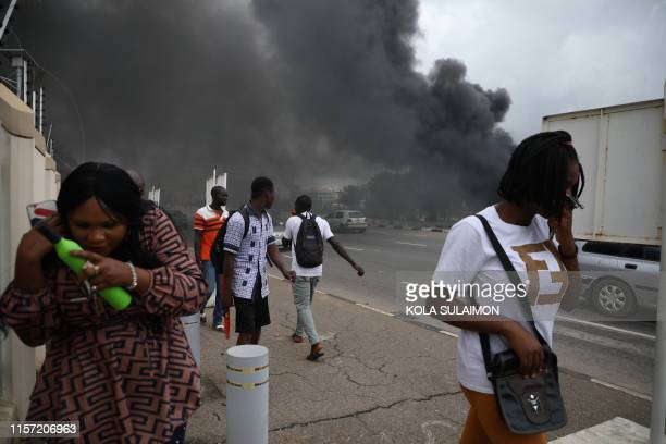 People walk past a fire service station set ablaze by members of the shiite Islamic Movement of Nigeria during clashes with the police in the streets...