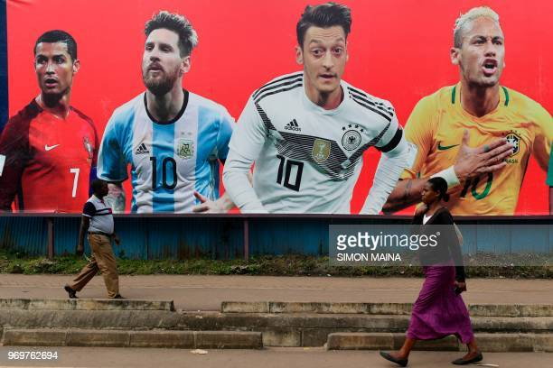 People walk past a football billboard displaying Portugal's forward Cristiano Ronaldo Argentina's forward Lionel Messi Germany's midfielder Mesut...