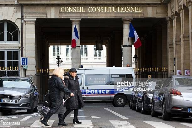 People walk past a French police vehicle outside the Constitutional Council in Paris on December 23 2015 The French cabinet backed reform proposals...
