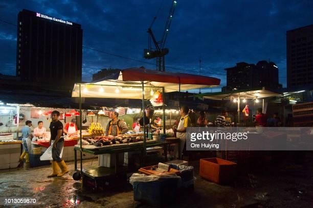 People walk past a fresh produce market on July 30 2018 in Kuala Lumpur Malaysia Malaysia's former prime minister Najib Razak has been under...