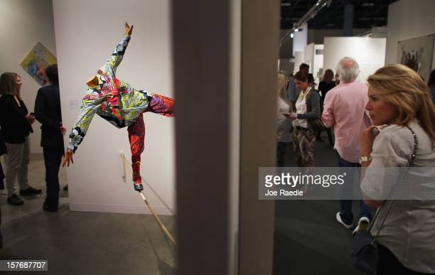 """People walk past a gallery with an art piece titled, """"Boy on Tightrope"""" by Yinka Shonibare as Art Basel opens at the Miami Beach Convention Center on..."""