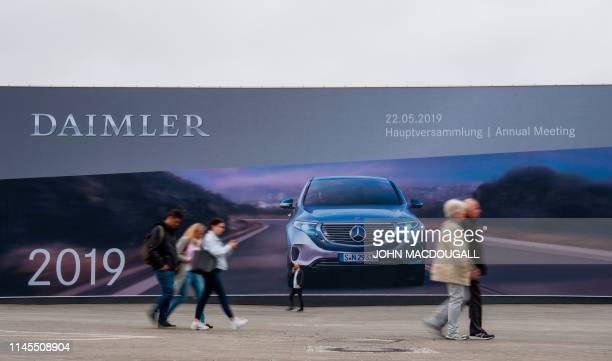 People walk past a giant billboard advertising German car manufacturing giant Daimler's annual general meeting on May 22 2019 in Berlin Daimler boss...
