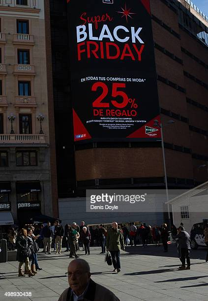 People walk past a giant electronic screen at the El Corte Ingles department store in Callao square advertising 'Black Friday' discounts November 27...