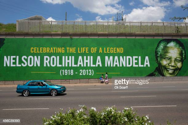 People walk past a giant poster of Nelson Mandela as the former South African president lies in state for a final day at Union Buildings on December...