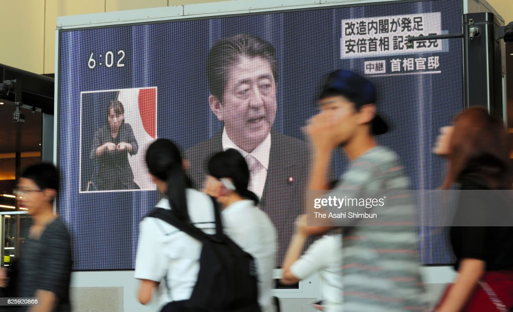 People walk past a giant screen broadcasting the news of Prime Minister Shinzo Abe reshuffling his cabinet on August 3, 2017 in Osaka, Japan. Prime Minister Shinzo Abe reshuffles his Cabinet appointing ministers from outside his close circle of political allies in a bid to halt declining support ratings.