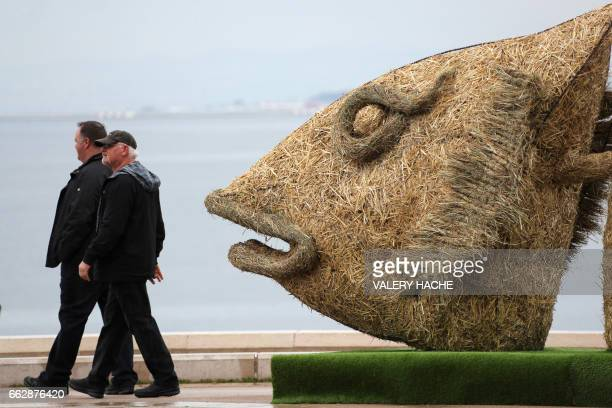 People walk past a giant straw fish created by French sculptor Christian Burger with the collaboration of French sculptors Philippe Minier and Lucile...