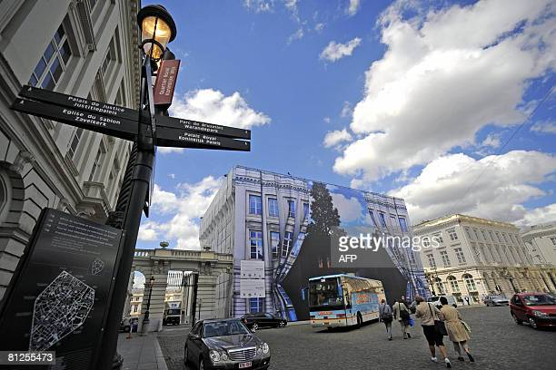 People walk past a giant tarpaulin bearing one of Belgian surrealist master Rene Magritte's most celebrated works Empire of Light in Brussels on May...