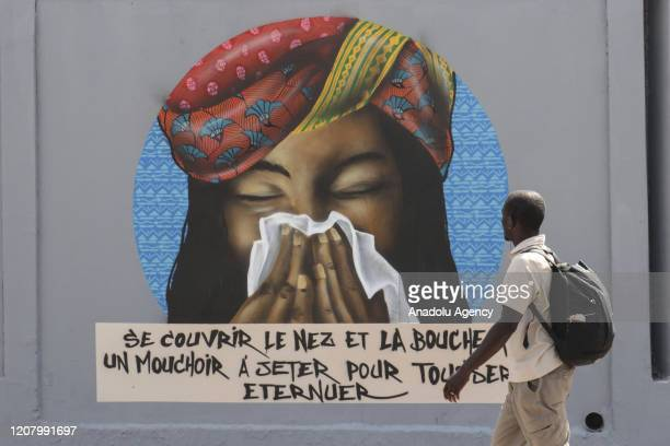 People walk past a graffiti on the wall depicting hygienic steps which will be followed to struggle against COVID19 in Dakar Senegal on March 22 2020...