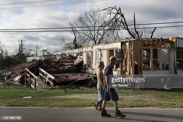 People walk past a home destroyed by Hurricane Michael on October 11 2018 in Panama City Florida The hurricane hit the Florida Panhandle as a...