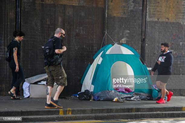 People walk past a homeless person's tent under a bridge in London.