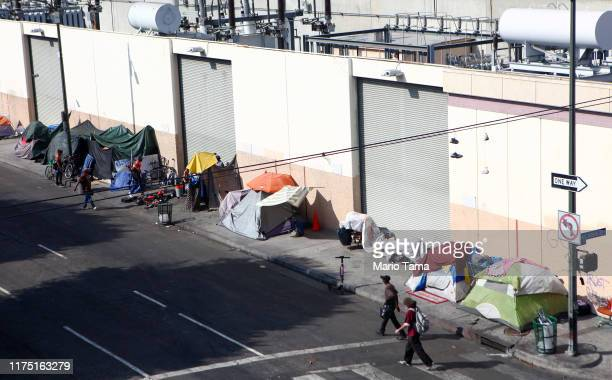 People walk past a homeless tent encampment in Skid Row on September 16 2019 in Los Angeles California Skid Row is home to thousands who either live...